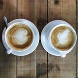 Δύο φλυτζάνια του cappuccino με τα περίπλοκα σχέδια αφρού σε έναν πίνακα φιαγμένο από κατά προσέγγιση αντιμετωπισμένους πίνακες στοκ εικόνες