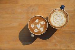 Δύο φλυτζάνι του διαφορετικού καφέ που είναι γάλα cappuccino και καραμέλας latte στον ξύλινο αγροτικό πίνακα το πρωί με το ισχυρό στοκ φωτογραφία