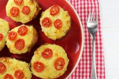 Δύο φορές ψημένες πατάτες με το τυρί και ντομάτες σε ένα κόκκινο πιάτο Στοκ εικόνα με δικαίωμα ελεύθερης χρήσης