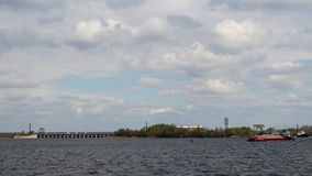 Δύο φορτηγίδες στον ποταμό στο υπόβαθρο του φράγματος απόθεμα βίντεο