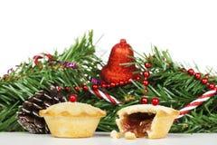 Δύο φρέσκα κομματιάζουν τις πίτες μπροστά από τις διακοσμήσεις Χριστουγέννων Στοκ Εικόνα