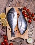 Δύο φρέσκα χοιρομητέρα-επικεφαλής bream ψάρια στον τέμνοντα πίνακα με την ντομάτα λεμονιών, κρεμμυδιών και κερασιών Στοκ φωτογραφία με δικαίωμα ελεύθερης χρήσης