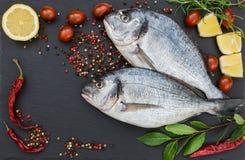 Δύο φρέσκα ψάρια dorado στον τέμνοντα πίνακα πλακών Τοπ όψη Στοκ Φωτογραφίες