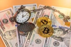 Δύο φυσικά χρυσά bitcoins με το ρολόι τσεπών στα αμερικανικά δολάρια Στοκ Φωτογραφίες