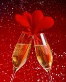 Δύο φλάουτα σαμπάνιας με τις χρυσές φυσαλίδες και τις κόκκινες καρδιές βελούδου κάνουν τις ευθυμίες στο κόκκινο υπόβαθρο bokeh Στοκ Φωτογραφίες