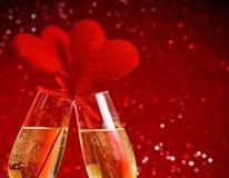 Δύο φλάουτα σαμπάνιας με τις χρυσές φυσαλίδες και τις κόκκινες καρδιές βελούδου κάνουν τις ευθυμίες στο κόκκινο υπόβαθρο bokeh Στοκ Εικόνες