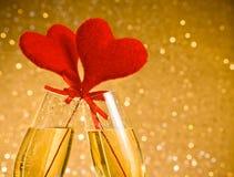 Δύο φλάουτα σαμπάνιας με τις χρυσές φυσαλίδες και τις κόκκινες καρδιές βελούδου κάνουν τις ευθυμίες στο χρυσό υπόβαθρο bokeh Στοκ Φωτογραφία