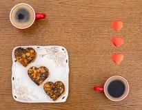 Δύο φλιτζάνια του καφέ, ένα τετραγωνικό πιάτο με τα κέικ και τις καρδιές ημέρας βαλεντίνων του ST σε ένα wo Στοκ Φωτογραφίες