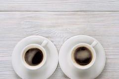 Δύο φλιτζάνια του καφέ με τον αφρό σε έναν άσπρο ξύλινο πίνακα Στοκ Εικόνες
