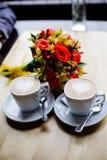 Δύο φλιτζάνια του καφέ στον πίνακα και μια ανθοδέσμη Στοκ φωτογραφίες με δικαίωμα ελεύθερης χρήσης