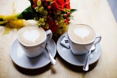 Δύο φλιτζάνια του καφέ στον πίνακα και μια ανθοδέσμη Στοκ Εικόνες