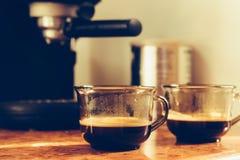 Δύο φλιτζάνια του καφέ στον πίνακα κοντά στη μηχανή καφέ Στοκ Εικόνες
