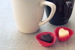 Δύο φλυτζάνια και δύο καρδιά-διαμορφωμένες σοκολάτες Στοκ Φωτογραφίες
