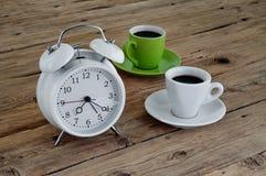 Δύο φλυτζάνια του espresso με ένα ξυπνητήρι Στοκ Εικόνες