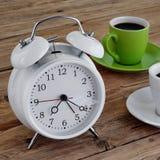 Δύο φλυτζάνια του espresso με ένα ξυπνητήρι Στοκ Φωτογραφίες