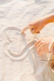 Δύο χέρια επισύρουν την προσοχή την καρδιά στην κινηματογράφηση σε πρώτο πλάνο άμμου Στοκ Φωτογραφία