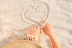 Δύο χέρια επισύρουν την προσοχή την καρδιά στην κινηματογράφηση σε πρώτο πλάνο άμμου Στοκ φωτογραφία με δικαίωμα ελεύθερης χρήσης