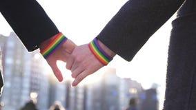 Δύο χέρια μαζί με τα βραχιόλια LGBT στα πλαίσια της οδού και του ήλιου απόθεμα βίντεο