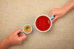 Δύο χέρια με τον καφέ espresso και τα μαύρα φλυτζάνια τσαγιού Στοκ Φωτογραφίες