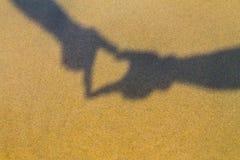 Δύο χέρια που διαμορφώνουν μια σκιά καρδιών ή ένα σύμβολο αγάπης στην παραλία Χρόνος διακοπών παγωμένες γυναίκες χρονικών διακοπώ Στοκ Εικόνα