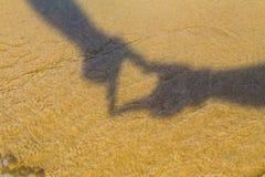 Δύο χέρια που διαμορφώνουν μια σκιά καρδιών ή ένα σύμβολο αγάπης στην παραλία Χρόνος διακοπών παγωμένες γυναίκες χρονικών διακοπώ Στοκ Φωτογραφία