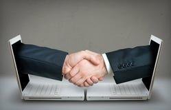 Δύο χέρια που κάνουν μια διαπραγμάτευση μέσω Διαδικτύου Στοκ εικόνα με δικαίωμα ελεύθερης χρήσης