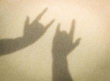 Δύο χέρια που κάνουν τη σκιά να υπογράψει σ' αγαπώ στην άμμο στην παραλία Στοκ Φωτογραφίες