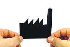 Δύο χέρια που κρατούν ένα μαύρο εργοστάσιο εγγράφου διαμορφωμένο Στοκ Εικόνες