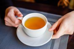 Δύο χέρια που κρατούν ένα φλυτζάνι πορσελάνης στο χρόνο τσαγιού στον καφέ Στοκ εικόνα με δικαίωμα ελεύθερης χρήσης