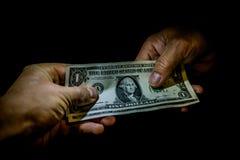 Δύο χέρια που παραδίδουν τα αμερικανικά τραπεζογραμμάτια δολαρίων ο ένας στον άλλο στοκ φωτογραφία