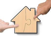 Δύο χέρια που συγκεντρώνουν τους ξύλινους γρίφους μορφής σπιτιών Στοκ Εικόνες