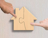 Δύο χέρια που συγκεντρώνουν τους ξύλινους γρίφους μορφής σπιτιών Στοκ φωτογραφία με δικαίωμα ελεύθερης χρήσης