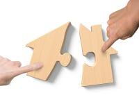 Δύο χέρια που συγκεντρώνουν τους ξύλινους γρίφους μορφής σπιτιών Στοκ Φωτογραφία