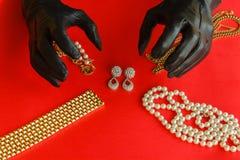 Δύο χέρια που τυλίγονται στα μαύρα γάντια πρόκειται να κλέψουν τα κοσμήματα Στοκ Εικόνες