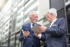 Δύο χαμογελώντας ανώτεροι επιχειρηματίες που εργάζονται σε μια ταμπλέτα και μια συζήτηση στοκ φωτογραφίες