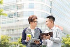 Δύο χαμογελώντας αρσενικοί συνάδελφοι εργασίας που μιλούν υπαίθρια μαζί άνω του α στοκ εικόνες