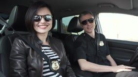 Δύο χαμογελώντας αστυνομικοί που κάθονται στο αυτοκίνητο φιλμ μικρού μήκους