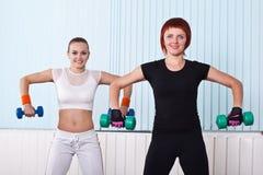 Δύο χαμογελώντας γυναίκες ικανότητας που ανυψώνουν τους αλτήρες Στοκ Φωτογραφία