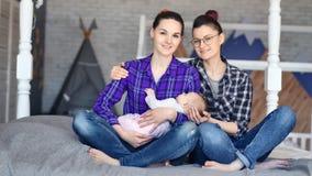 Δύο χαμογελώντας θηλυκό γονέας που απολαμβάνει την εκμετάλλευση μητρότητας που κοιμάται λίγο χαριτωμένο μωρό με το χέρι φιλμ μικρού μήκους