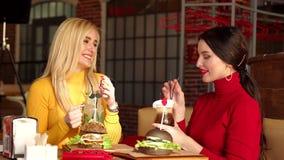 Δύο χαμογελώντας κορίτσια πίνουν τα κοκτέιλ και τρώνε τα burgers σε ένα φωτεινό εστιατόριο απόθεμα βίντεο