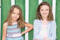 Δύο χαμογελώντας παιδιά στην πράσινη ξύλινη αδελφή παιδιών υποβάθρου εύθυμη ευτυχή από κοινού Στοκ εικόνες με δικαίωμα ελεύθερης χρήσης