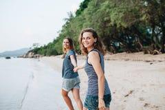 Δύο χαμογελώντας φίλοι που περπατούν ο ένας τον άλλον στην παραλία στοκ φωτογραφία