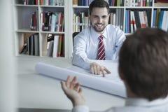 Δύο χαμογελώντας αρχιτέκτονες που συζητούν πέρα από ένα σχεδιάγραμμα στο γραφείο, Στοκ Εικόνες
