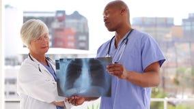 Δύο χαμογελώντας γιατροί που εξετάζουν μια ακτίνα X απόθεμα βίντεο