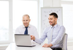 Δύο χαμογελώντας επιχειρηματίες με το lap-top στην αρχή Στοκ εικόνα με δικαίωμα ελεύθερης χρήσης