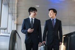 Δύο χαμογελώντας επιχειρηματίες που ενώνονται επάνω στην κυλιόμενη σκάλα Στοκ Φωτογραφία