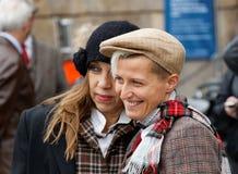 Δύο χαμογελώντας κυρίες που φορούν τα ντεμοντέ ενδύματα τουίντ Στοκ Εικόνες