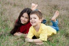 Δύο χαμογελώντας παιδιά στη χλόη φθινοπώρου Στοκ εικόνα με δικαίωμα ελεύθερης χρήσης