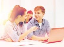 Δύο χαμογελώντας σπουδαστές με το φορητό προσωπικό υπολογιστή Στοκ φωτογραφία με δικαίωμα ελεύθερης χρήσης