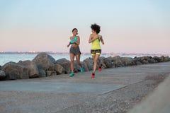 Δύο χαμογελώντας όμορφες γυναίκες ικανότητας που τρέχουν από κοινού Στοκ εικόνες με δικαίωμα ελεύθερης χρήσης